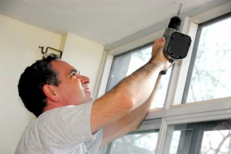 A man installing window shades.
