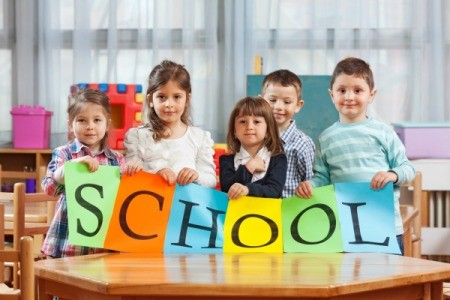Preschool kids sitting at a table holding a sign that says school.