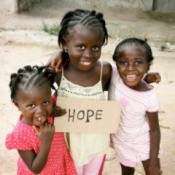 African children holding a sign that says hope.