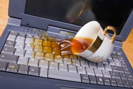 Tea spilling on a laptop computer keyboard.