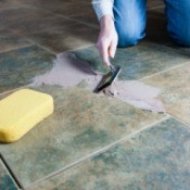 A handyman replacing floor grout.