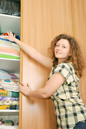 Woman Storing Bedding in Linen Closet