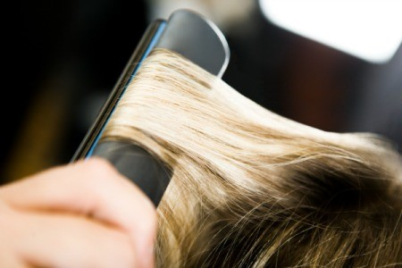 Using a flat iron on hair.