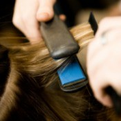 Using a flat iron to straighten hair.