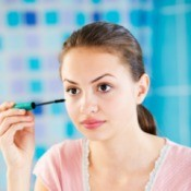 A teen girl putting on makeup.