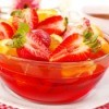 Jell-o salad with red jell-o, strawberries and oranges.