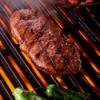 Tender rib eye steak on a grill.