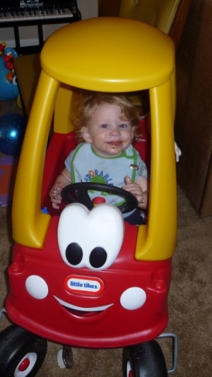Toddler in red and yellow Little Tikes car.