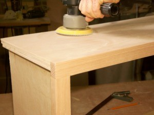 Sanding an oak plywood cabinet.