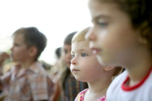 Children watching a show at a park.