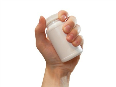 Photo of a hand holding a supplement bottle.