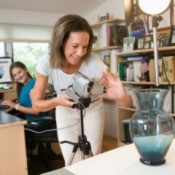 A woman taking a photo of a vase to post it on eBay.