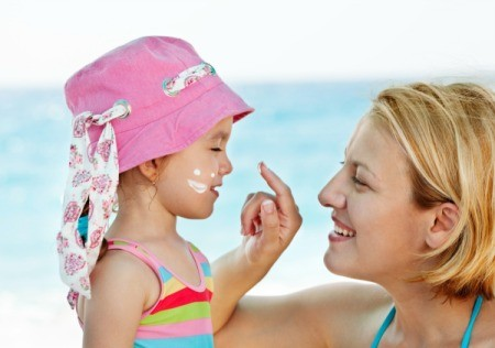 A mom putting sunscreen on her child.
