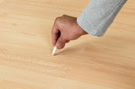 Fixing a scratch on laminate flooring.