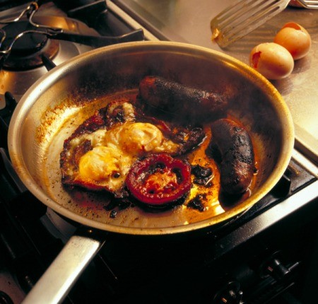 Breakfast burnt and stuck to the bottom of a pan.
