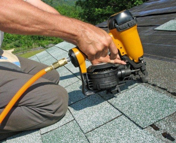 A man with a nail gun performing roof repairs.