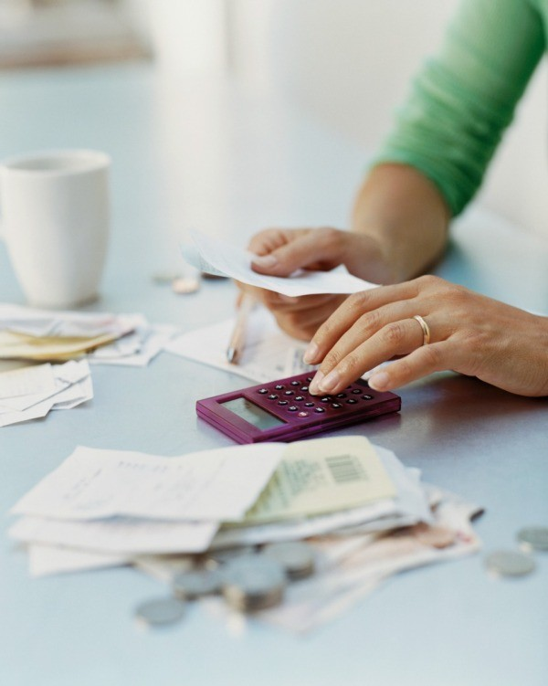 A woman using a calculator to add up expenses.