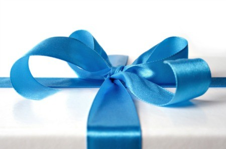 A wedding gift wrapped with white paper and a blue ribbon tied in a bow.