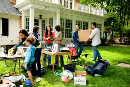Yard sale on the front lawn of a house.