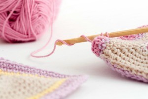 Crochet hook and pink yard.