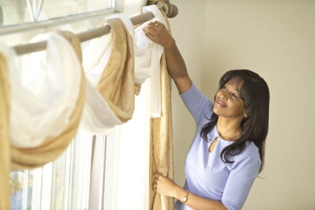 Woman hanging a window treatment.