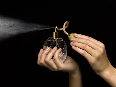 Woman spraying perfume into the air.