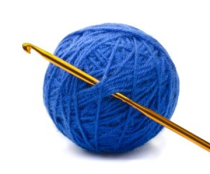 Ball of blue yarn with crochet hook.