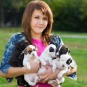 Young woman holding puppies.