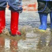Two kids standing in the rain wearing colorful rain boots.