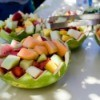Fruit salad bowls made in carved out watermelons at a large outdoor birthday party.