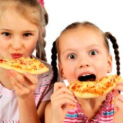 Two girls eating pizza.