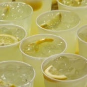 Lemonade cups on a table for serving to a large group.