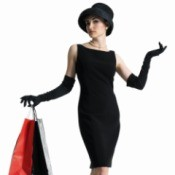 Woman in a black dress holding shopping bags.