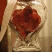 Heart shaped bottle with red flower.
