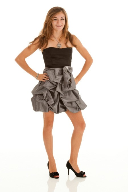 A girl wearing a homecoming dress.
