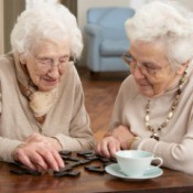 Two elderly women playing dominos.