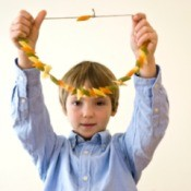 Boy holding up a Pasta Necklace