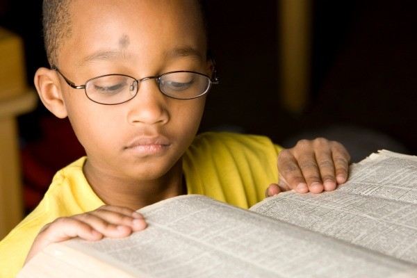 Boy reading a dictionary.