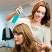 A hairdresser applying hairspray to a client in a salon.