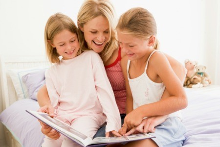 A babysitter reading to two girls.