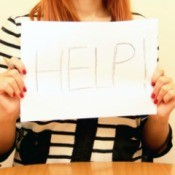 A woman holding a help sign.