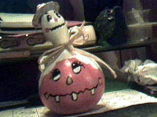Ghost painted on neck of gourd the bottom of which is painted as a Jack O Lantern.