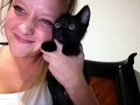 Young woman holding black kitten.