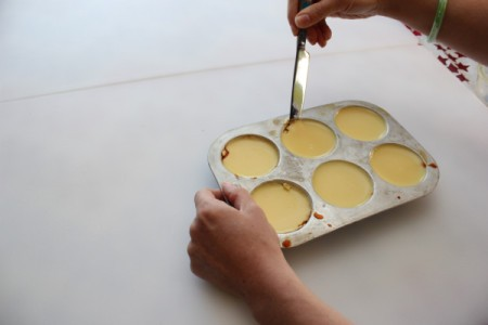 Loosening flan in muffin pan with a knife.
