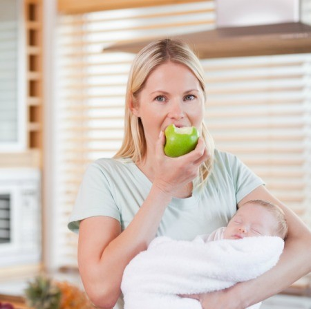 A woman eating an apple with her baby.