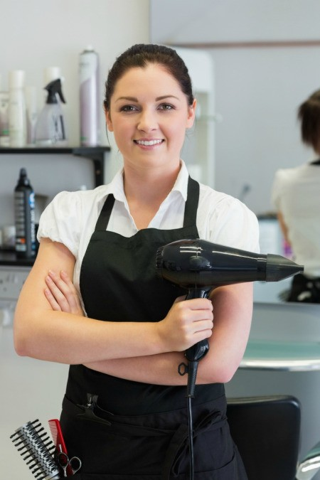 Photo of a hair stylist holding a blow dryer.