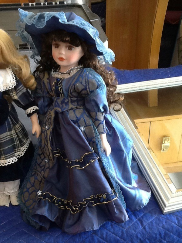 Period doll in blue outfit.