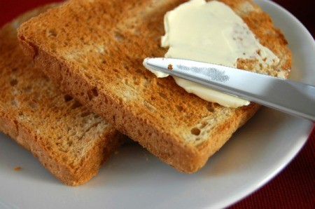 Spreading button on to a piece of toast.