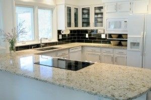 A nice kitchen with granite countertops and white cabinets.