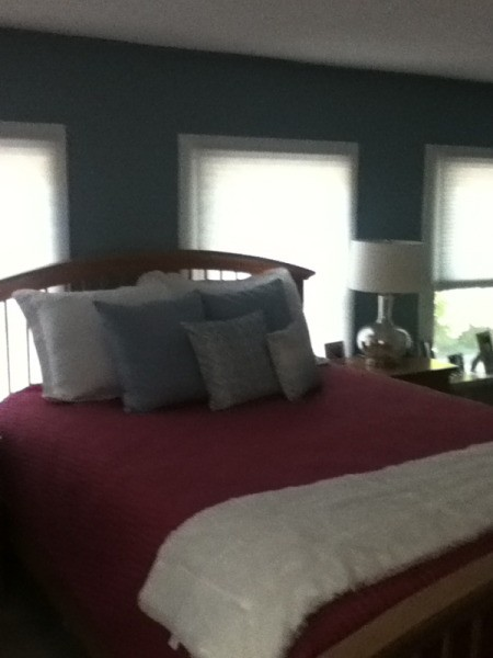 Photo of bed and windows behind it.